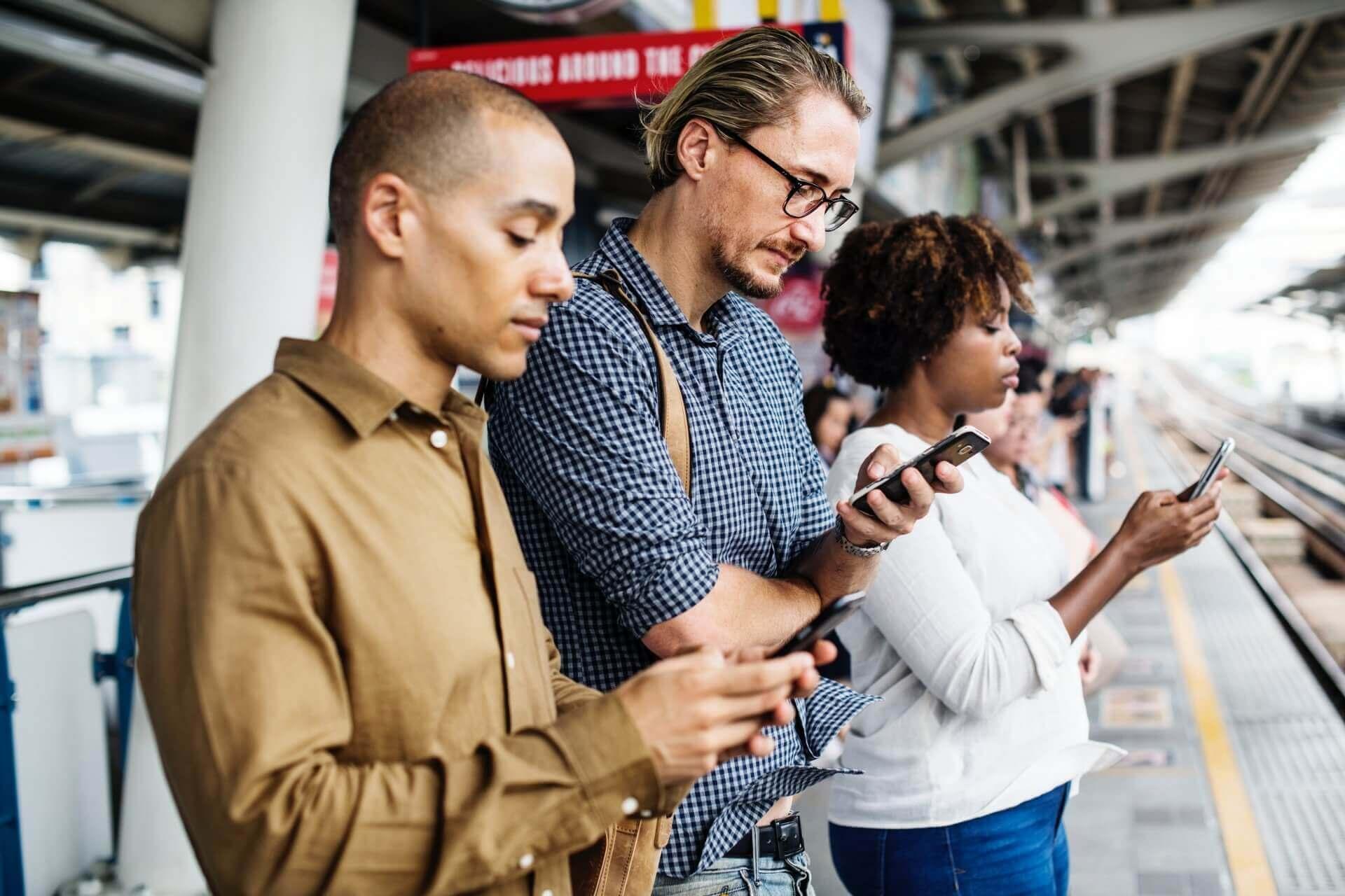 Big Data im E-Commerce wird über drei Personen visualisiert, die ein Smartphone am Gleis eines Bahnhofs nutzen.