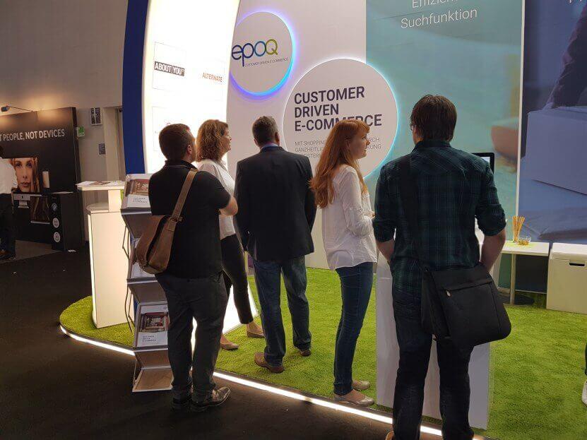 Bild von dem epoq Messestand auf der dmexco 2016, bei dem mehrere Leute im Gespräch über eine ganzheitlich personalisierte digitale Customer Journey zu sehen sind.