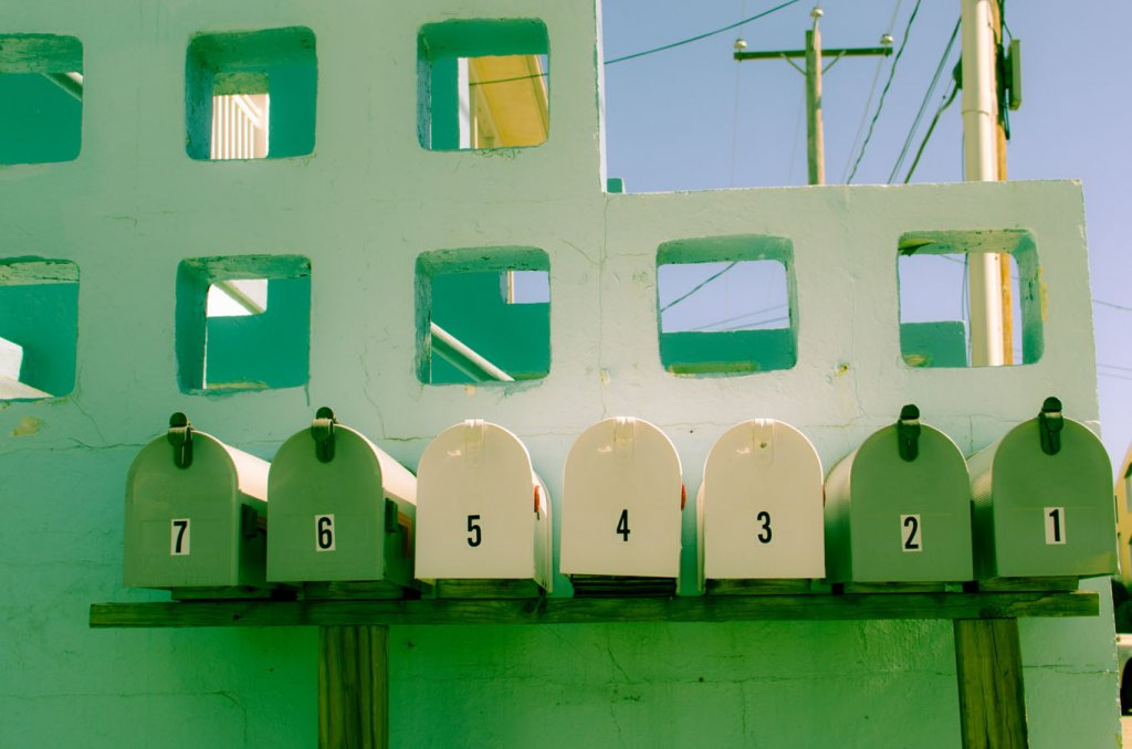 Von 1 bis 7 nummerierte, grüne und weiße Briefkästen sind vor einer Mauer aufgestellt als Symbol für relevanten Inhalt in der E-Mail