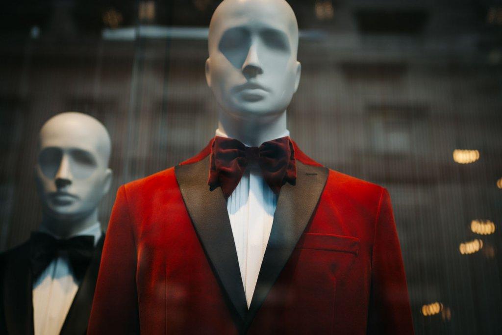 Eine Schaufensterpuppe in rotem Anzug und roter Fliege steht im Vordergrund. Eine weitere in schwarzem Anzug und schwarzer Fliege steht seitlich dahinter