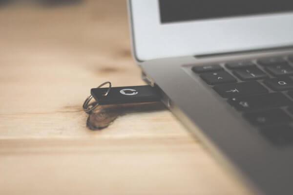 USB-Stick, der an ein Notebook angeschlossen ist in einer Nahaufnahme.