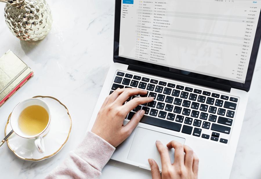 Das Bild zeigt einen Laptop, an dem eine Person arbeitet. Auf dem Bildschirm ist ein E-Mail-Programm geöffnet, das verschiedene E-Mail-Marketing-Beispiele zeigt.