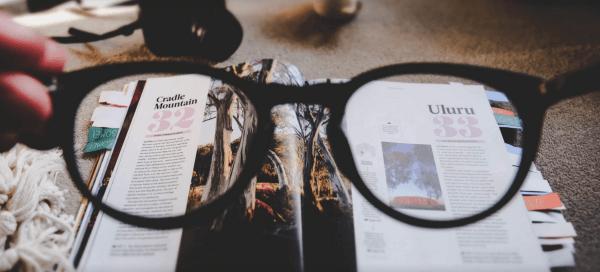 Eine Brille wird vor eine Zeitschrift gehalten und steht somit symbolisch für eine schnelle und fokusierte Suche durch die intelligente Suche von epoq.