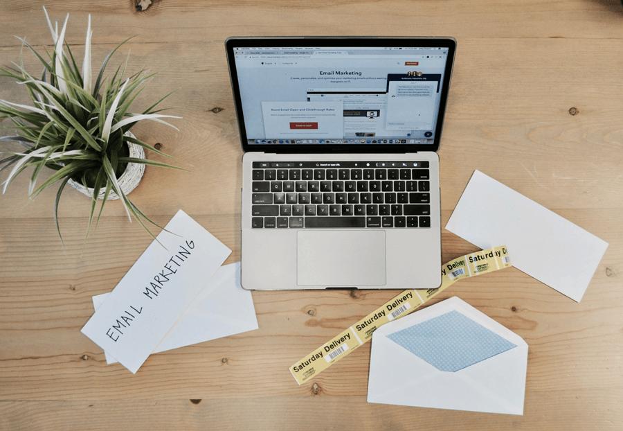 Das Bild zeigt einen Laptop sowie weitere Schreibtischutensilien. Auf dem Bildschirm erkennt man eine geöffnete Website, die das Thema E-Mail-Marketing-Automation behandelt.