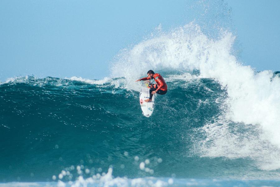 Das Bild zeigt einen Surfer, der mit seinem Surfbrett auf einer Welle reitet. Der Surfer trägt einen Neoprenanzug, der im Artikel zum Guided-Selling-System als Beispiel dient.