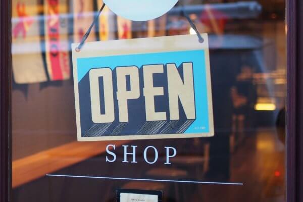 """Detailaufnahme eines Ladenstores von außen mit der Sicht auf die Eingangstüre aus Glas mit Blick auf ein Schild """"Open"""""""