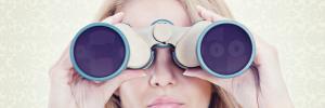Eine junge Frau hält ein Fernglas mit beiden Händen vor ihren Augen fest. Auch beim Online Shopping ist eine Hilfe bei der Suche notwendig. Wie das ganze am besten aussieht, kann auf passenden Events gelernt werden.
