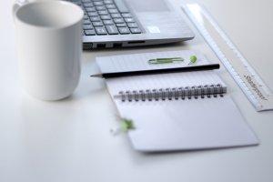Eine Tasse, Notizblock, Stift und ein Laptop. Alles sind Utensilien, die eine hohe Relevanz für die Büroarbeit besitzen.