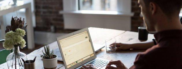Mann sitzt am Mac und schaut sich eine Web-Demo zu den epoq Produkten an: intelligente Suche, Guided Selling, Recommendation Engine und personalisierte E-Mail.