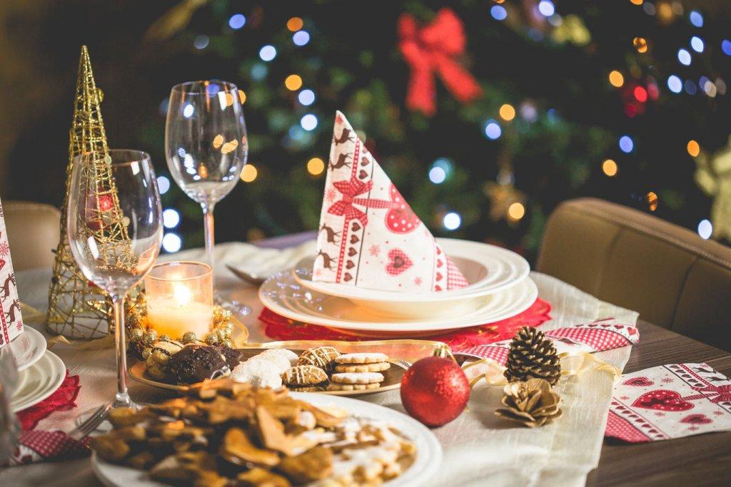 Es ist ein weihnachtlich gedeckter Tisch zu sehen. In der Mitte befindet sich ein Teller mit aufgestellter Serviette, links daneben stehen zwei Weingläser, vorne liegen Weihnachtsplätzchen auf einem Teller, daneben liegt Dekoration und im Hintergrund ist steht ein Weihnachtsbaum.