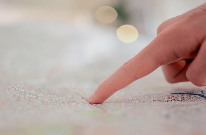 Eine Person zeigt auf einer Karte, wie das Customer Journey Mapping auf die Customer Experience.
