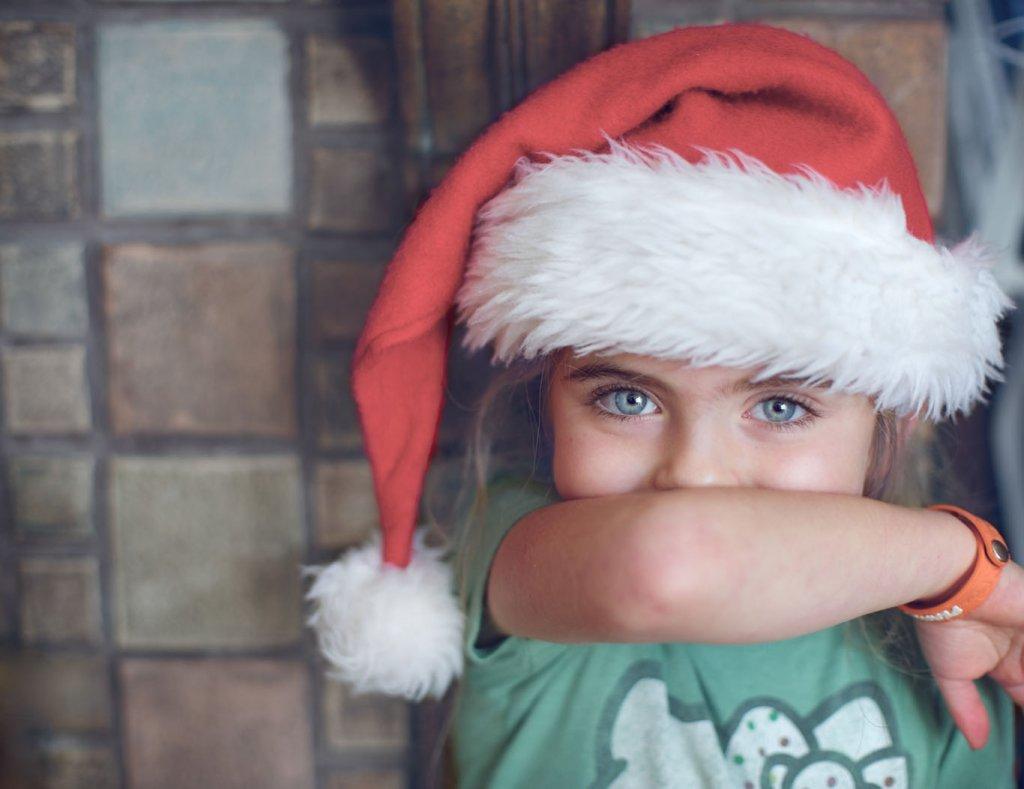 Ein kleines Mädchen mit Nikolausmütze auf dem Kopf hält sich den Arm vor Mund und Nase.