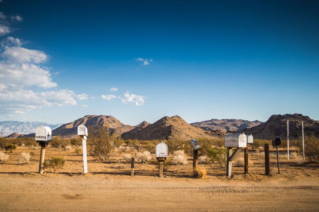 In einer Wüsternladschaft stehen nebeneinander 7 verschiedene Briefkästen. Im Hintergrund sind Berge und der blaue Himmel zu sehen.
