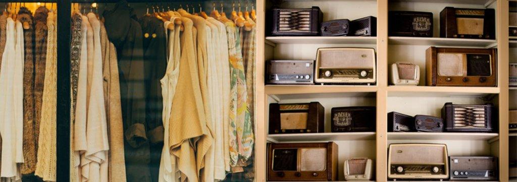 In einem Schrank hängt in der einen Hälfte Kleidung, in der anderen stehen in 8 Fächer geordnet verschiedene alte Radios. Personalisierung im Branchenvergleich, Modebranches vs. Elektronikbranche.