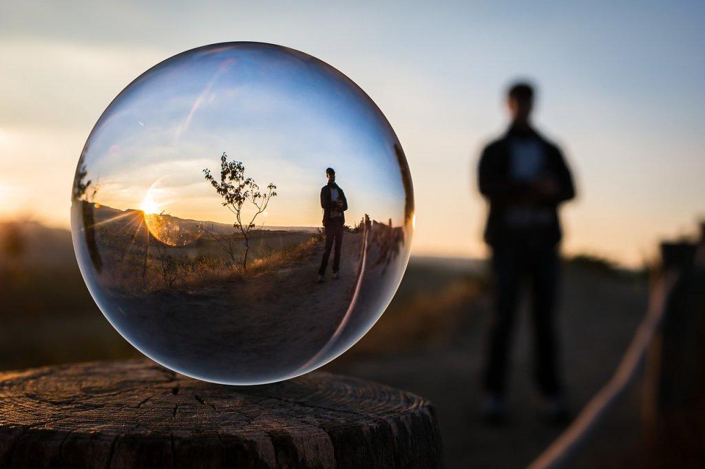 Eine Seifenblase zeigt eine Person die auf der Straße im Sonnenuntergang steht. Die Seifenblase symbolisiert die künstliche Intelligenz die auch in Online Shops für Recommendations eingesetzt wird.