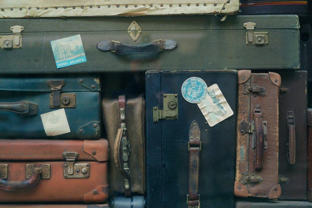 Viele aufeinandergestapelte Vintagekoffer in unterschiedlichen Größen, Formen und Farben. Sie stehen für die große Auswahl in Onlineshops, bei der ein Produktberater dem Kunden in der Entscheidung unterstützt.