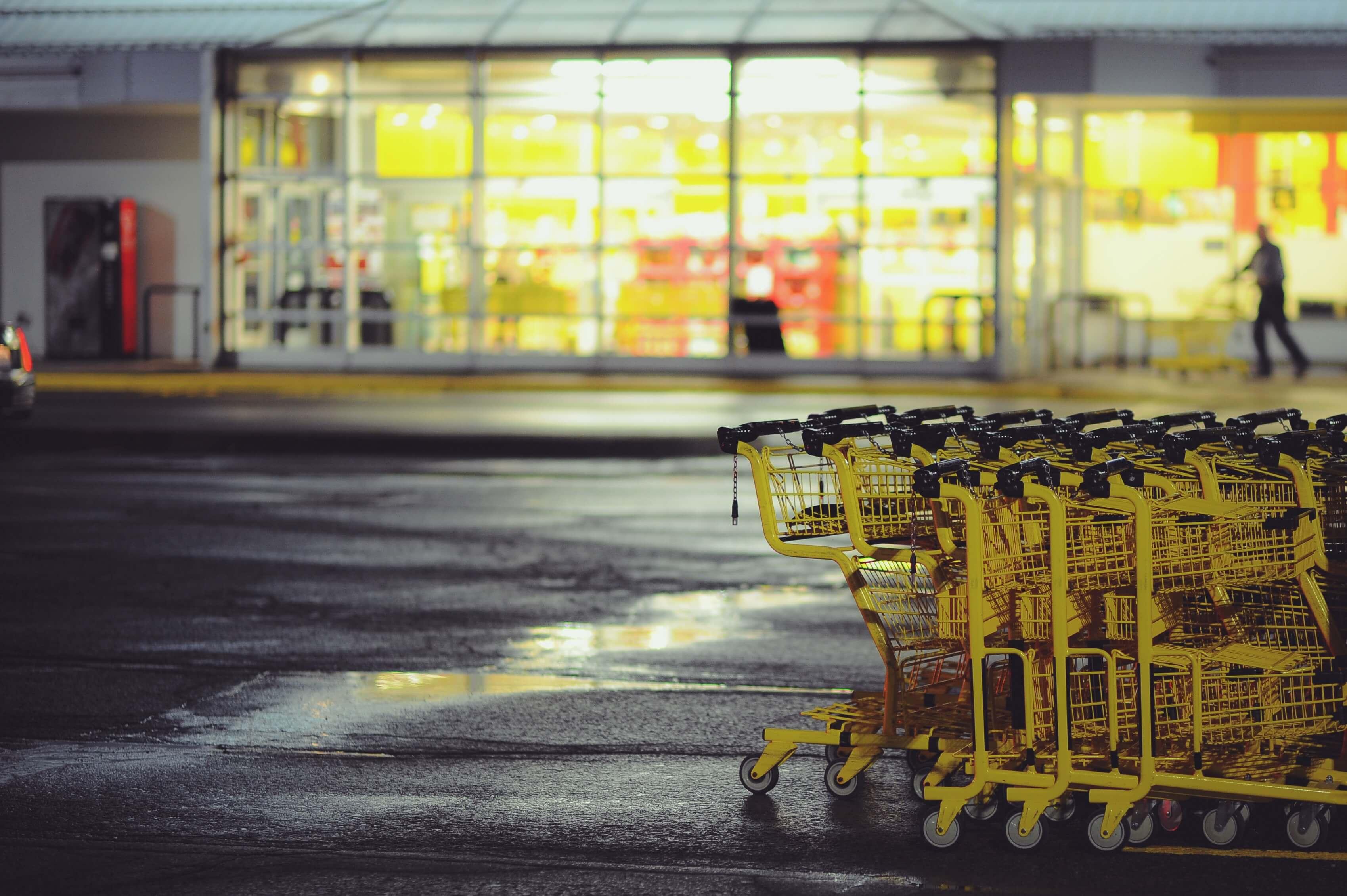 Gelbe Einkaufswagen stehen auf einem Parkplatz vor einem Geschäft. Durch eine Warenkorbabbruchmail sollen die Onlinekunden wieder zurück in den Shop geführt werden.