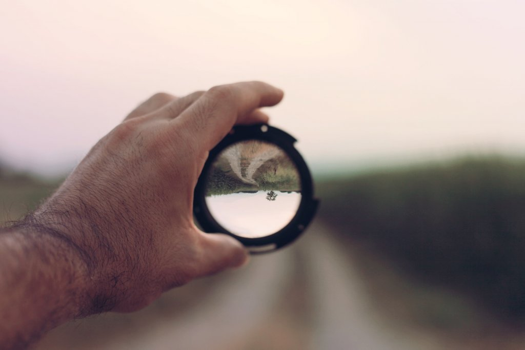 Eine Hand hält eine Fotolinse vor einen Feldweg, sodass der gewünschte Bereich scharf zu erkennen ist, wie auch bei der e-Commerce Site Search