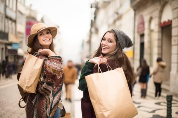 Zwei glückliche Frauen sind zufrieden mit ihrem Einkaufstag, wie sie es auch im Online Shopping durch Customer Experience Management sind.