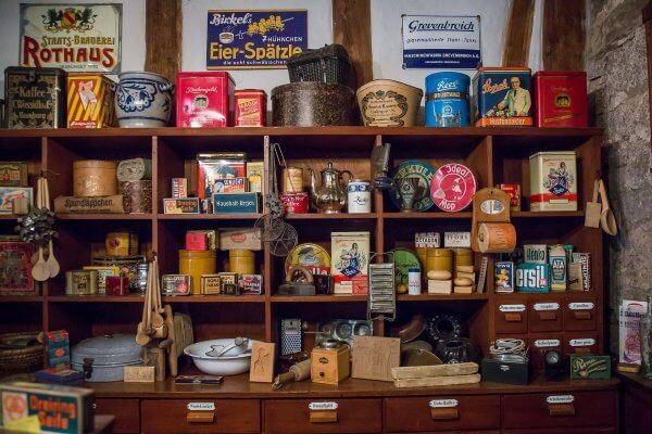 Ein Holzregal mit einer großen Auswahl an Lebensmitteln und Haushaltsprodukten, welches e-Commerce Recommendations in Online Shops symbolisiert.