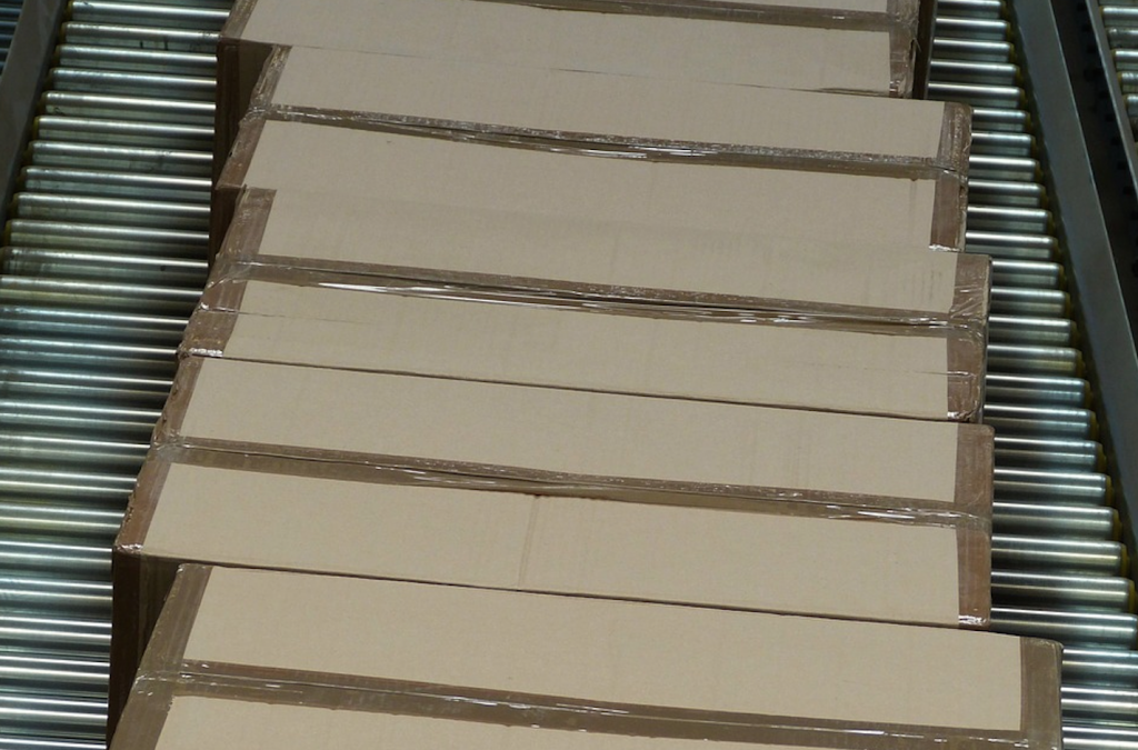 Auf dem Bild sieht man mehrere Pakete auf einem Laufband. Dies stellt einen Teil des Retourenmanagements dar.