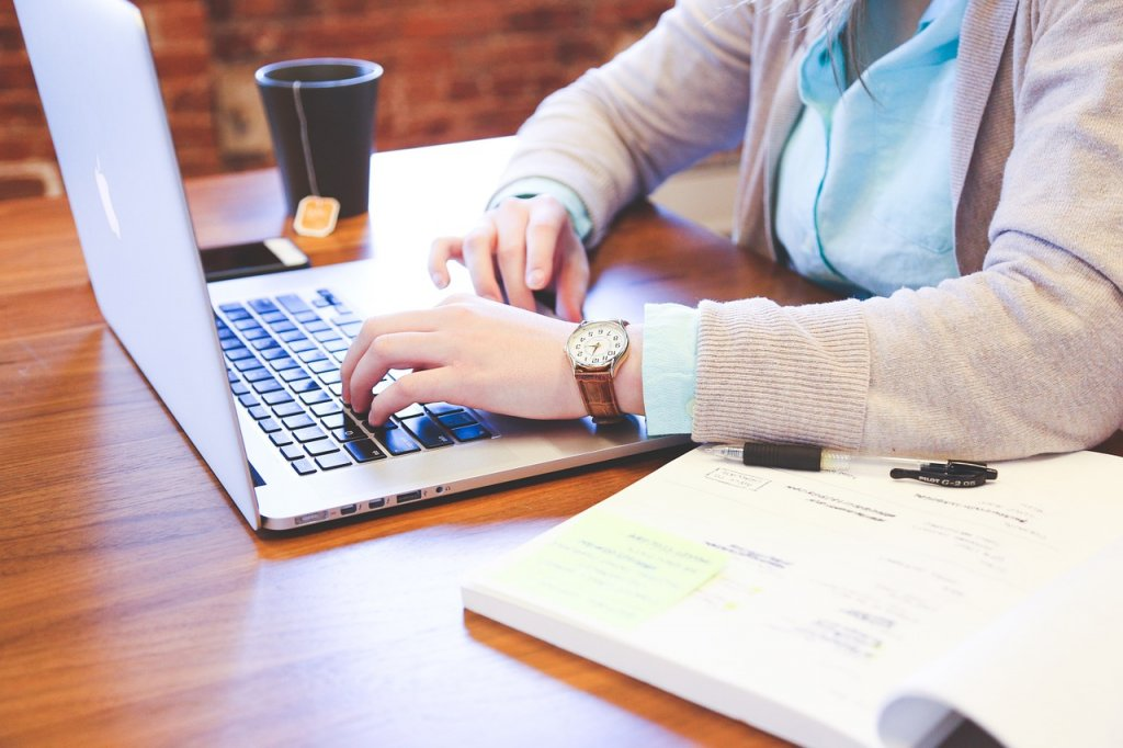 Eine Frau am McBook, die im B2B E-Commerce tätig ist.
