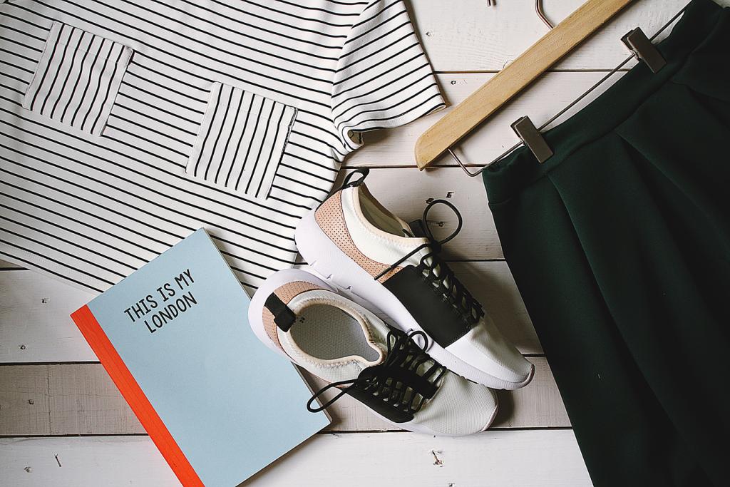 Das Titelbild des Artikels zum Empfehlungsmanagement zeigt mehrere Kleidungsstücke, Schuhe sowie ein Buch auf einem Holzboden.