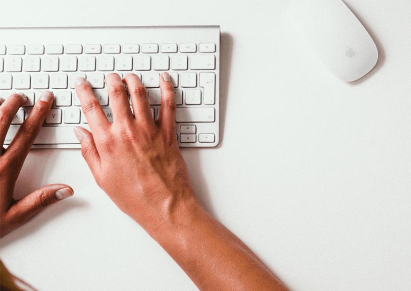 Person tippt auf Tastatur und löst durch Rechtschreibfehler fehlertolerante Suche aus