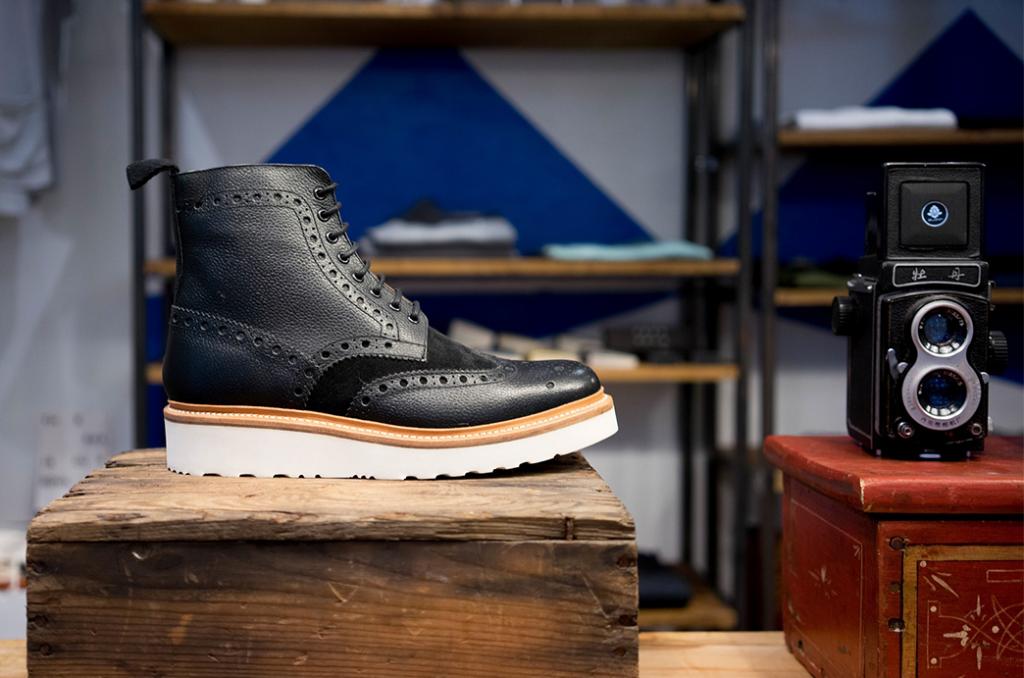 Ein schwarzer Schuh steht auf einem Holzklotz. Er wird auf dem Bild so gut dargestellt wie ein Produkt auf einer Produktdetailseite.