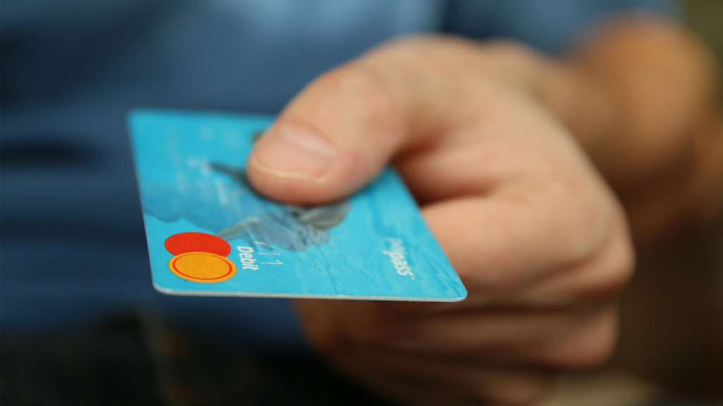 Das Bild zeigt eine Person, die eine Kreditkarte in einer Hand hält. Diese steht im übertragenen Sinn für den Checkout-Prozess im Online-Shop.