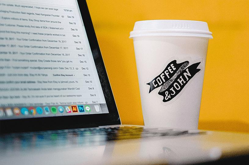 Ein Kaffeebecher und ein Laptop stehen vor einem gelben Hintergrund. Auf dem Laptop ist ein E-Mail-Programm mit vielen ungelesenen E-Mails zu sehen. Um hier herauszustechen, werden E-Mail-Marketing-Tipps benötigt.
