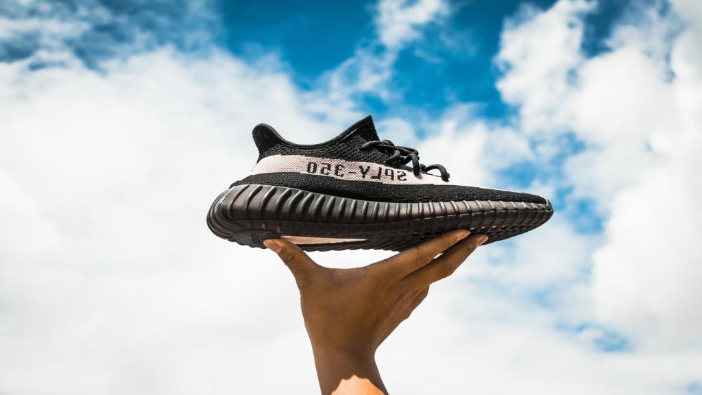 Eine Hand hält einen Sneaker in die Luft