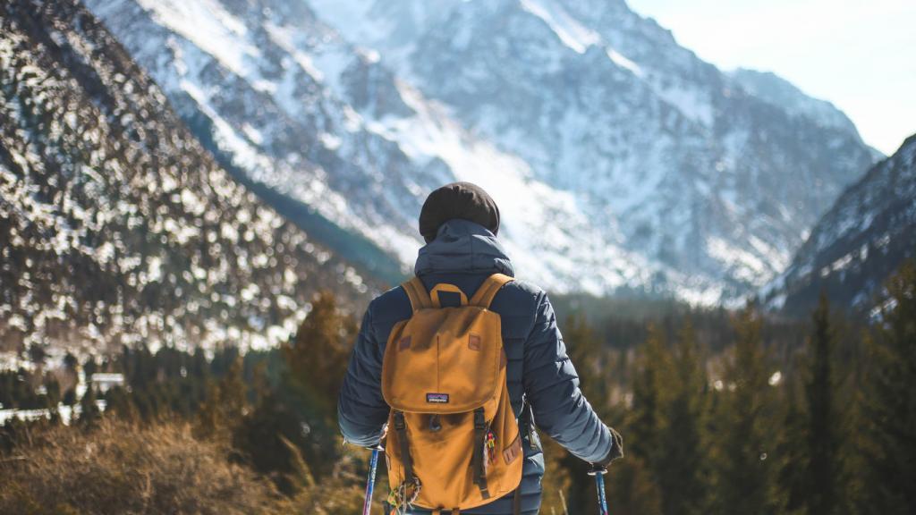 Ein Wanderer unterwegs in einem Gebirge mit Blick auf Berge