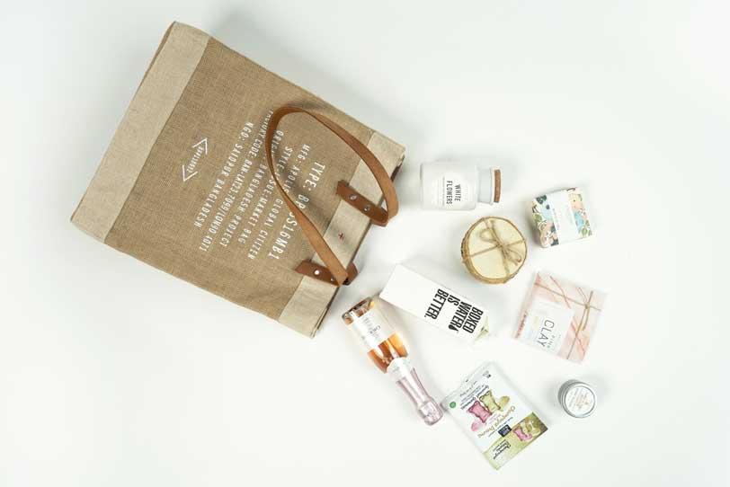Das Bild zeigt eine Einkaufstasche und verschiedene Produkte, die sinnbildlich für die Warenkorb Optimierung stehen.