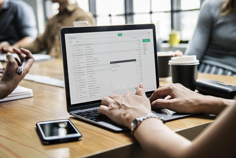 Eine Person sitzt vor einem Laptop auf dem ein E-Mail-Programm geöffnet ist und sieht sich verschiedene E-Mail-Kampagnen an.