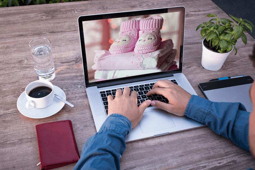 Ein Mann sitzt vor seinem Laptop, auf dem ein Bild von Kinderbekleidung zu sehen ist. Dieses erhält er als Empfehlung in Form einer Lifecycle-E-Mail, die seine aktuellen Bedürfnisse berücksichtigt.