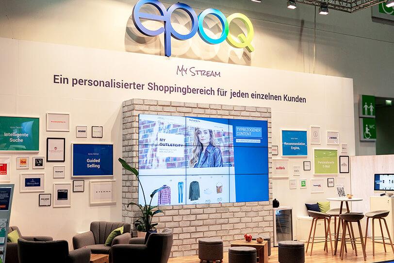 Das Bild zeigt den Stand von epoq auf der DMEXCO 2019. Der Stand ist wie ein Wohnzimmer aufgebaut mit verschiedenen Sitzmöglichkeiten und einem großen Bildschirm.