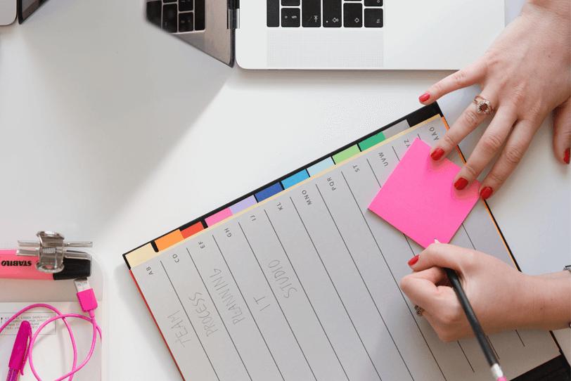 Das Bild zeigt einen Schreibtisch mit einem Laptop und einem Merkzettel, auf dem sich eine Person etwas notiert.