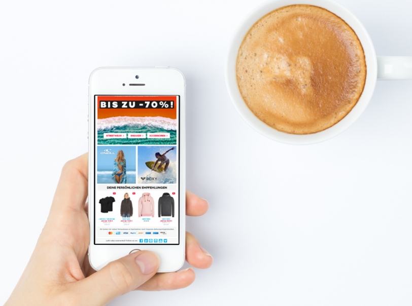 Das Bild zeigt ein Beispiel für Personalisierung. Dargestellt wird ein Smartphone, auf dem eine E-Mail geöffnet ist, in der personalisierte Empfehlungen ausgespielt werden.