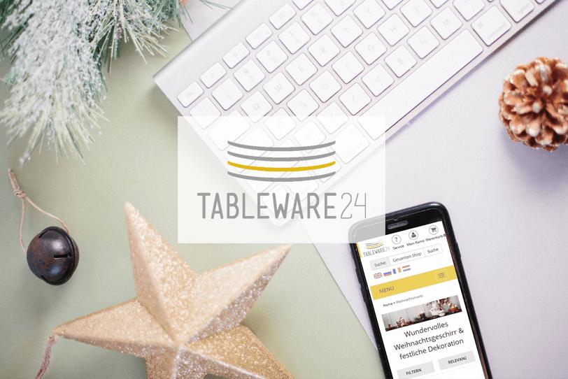 Das Bild zeigt einen weihnachtlich dekorierten Schreibtisch. Darauf liegt ein Smartphone, auf dem die Weihnachtsmarkt-Themenseite des Online Shops von Tableware24 zu sehen ist.