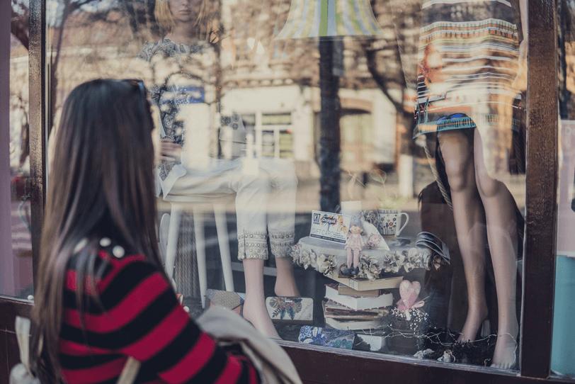 Das Bild zeigt eine Person, die vor einem Schaufenster steht – dieses steht im übertragenen Sinne für die Startseite des Online Shops, die optimal gestaltet werden sollte.