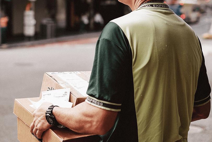 Das Bild zeigt eine Person mit Paketen in der Hand.